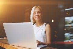使用便携式的网书的迷人的梦想的欧洲女性在休闲时间在咖啡馆 库存照片