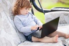 使用便携式计算机、孩子和技术的聪明的小孩女孩 库存图片