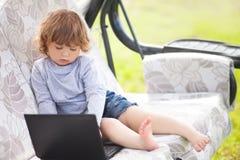 使用便携式计算机、孩子和技术的聪明的小孩女孩 免版税库存图片
