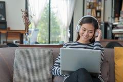 使用便携式计算机和听的音乐的亚裔少年女孩  免版税库存照片