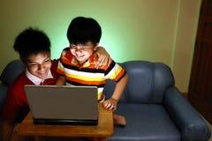 使用便携式计算机和微笑的两个年轻男孩 免版税库存照片
