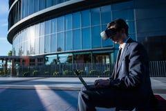 使用便携式计算机和虚拟现实玻璃的商人 免版税图库摄影