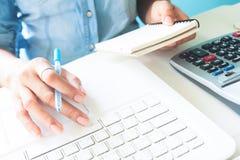 使用便携式计算机和计算器,事务的女商人  免版税图库摄影