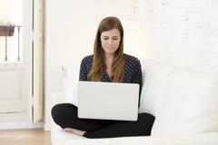 使用便携式计算机微笑的网络现代客厅的愉快的美丽的30s妇女在家放松了 库存照片