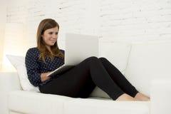 使用便携式计算机微笑的网络现代客厅的愉快的美丽的30s妇女在家放松了 库存图片