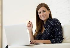使用便携式计算机微笑的网络现代客厅的愉快的美丽的30s妇女在家放松了 免版税库存图片