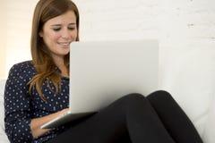使用便携式计算机微笑的网络现代客厅的愉快的美丽的30s妇女在家放松了 免版税库存照片