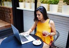 使用便携式计算机的一位年轻女性自由职业者的画象为距离工作,当坐在现代咖啡店内部时, 免版税库存图片