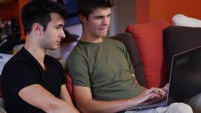 使用便携式计算机的两个年轻男性朋友 股票录像