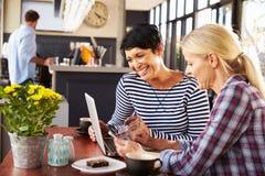 使用便携式计算机的两名妇女在咖啡店 图库摄影