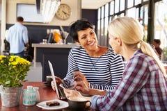 使用便携式计算机的两名妇女在咖啡店 库存图片