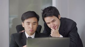 使用便携式计算机的严肃的被注重的两商人对工作计划 股票视频
