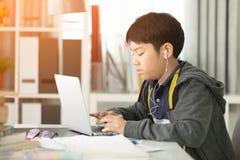 使用便携式计算机的亚裔逗人喜爱的男孩 免版税库存图片