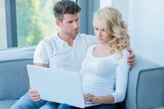 使用便携式计算机的关心的年轻夫妇 库存照片