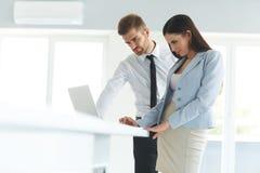 使用便携式计算机的商人在Ofiice 免版税图库摄影