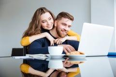 使用便携式计算机的夫妇在家 库存图片