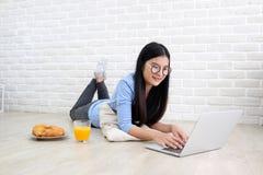 使用便携式计算机的年轻亚裔妇女坐在丝毫前面 免版税图库摄影