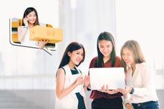 使用便携式计算机的年轻亚裔妇女或工友一起在网上购物 企业主女孩证实购买订单 免版税图库摄影