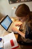 使用便携式计算机的年轻白肤金发的妇女做学校家庭作业和看在教科书 免版税库存照片