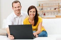 使用便携式计算机的微笑的夫妇 免版税库存照片