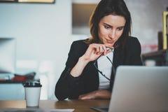 使用便携式计算机的微笑的美丽的女实业家在现代办公室 被弄脏的背景 水平 库存照片