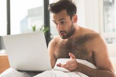 使用便携式计算机的惊奇的商人在卧室 库存照片