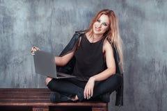 使用便携式计算机的愉快的美丽的少妇和有休息,当坐和放松在顶楼葡萄酒地方时 库存图片