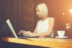 使用便携式计算机的美丽的聪明的女学生为coursework做准备 免版税库存照片