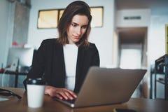 使用便携式计算机的英俊的女实业家画象在现代办公室 被弄脏的背景 水平 免版税库存图片