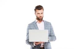 使用便携式计算机的被集中的年轻人 免版税库存图片