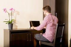 使用便携式计算机的年轻人在一个亚洲被称呼的旅馆客房 免版税库存照片