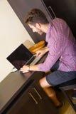 使用便携式计算机的年轻人在一个亚洲被称呼的旅馆客房 库存照片