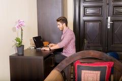 使用便携式计算机的年轻人在一个亚洲被称呼的旅馆客房 库存图片