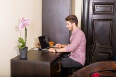 使用便携式计算机的年轻人在一个亚洲被称呼的旅馆客房 免版税图库摄影