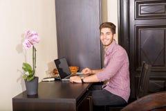 使用便携式计算机的年轻人在一个亚洲被称呼的旅馆客房 免版税库存图片