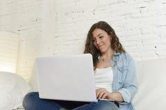 使用便携式计算机的年轻可爱的西班牙妇女放松的工作坐家庭长沙发 免版税库存照片