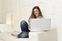 使用便携式计算机的年轻可爱的西班牙妇女放松的工作坐家庭长沙发 免版税库存图片
