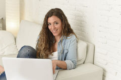 使用便携式计算机的年轻可爱的西班牙妇女放松的工作坐家庭长沙发 库存图片