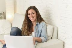 使用便携式计算机的年轻可爱的西班牙妇女放松的工作坐家庭长沙发 库存照片
