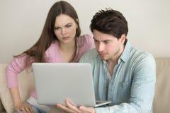 使用便携式计算机的年轻夫妇,有问题,急切和 免版税库存照片