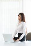 使用便携式计算机的年轻女商人 免版税库存照片