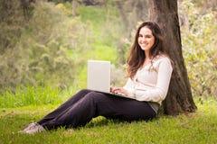 使用便携式计算机的年轻美丽的妇女在公园 免版税库存照片
