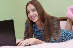 使用便携式计算机的年轻美丽的微笑的妇女说谎在床上 库存照片