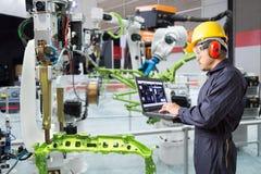 使用便携式计算机维护自动机器人韩的工程师 免版税库存图片
