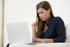 使用便携式计算机网络或网上互联网的妇女在家购物长沙发 免版税图库摄影
