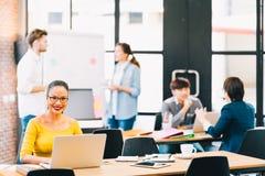 使用便携式计算机,当年轻不同种族的企业同事的微笑的亚裔妇女在背景 库存图片
