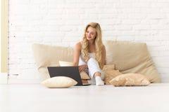 使用便携式计算机,美丽的女孩愉快微笑,年轻白肤金发的妇女坐在枕头的地板 免版税库存图片