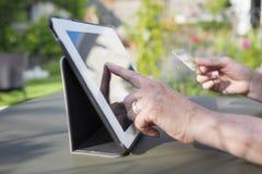 使用信用卡和片剂个人计算机的妇女前辈在网上购物 免版税库存图片