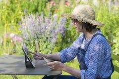 使用信用卡和片剂个人计算机的妇女前辈在网上购物 库存图片