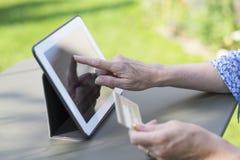 使用信用卡和片剂个人计算机的妇女前辈在网上购物 免版税库存照片